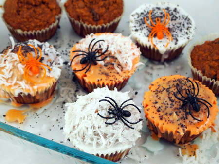 A batch of fresh homemade cupcakes being decorated for Halloween with spiders, colored frosting, and sprinkles.