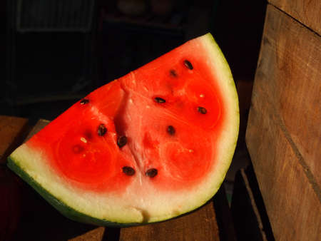 A juicy pink slice of watermelon peeps from the shadows in an old wooden barn on a late summer afternoon.  Stock Photo