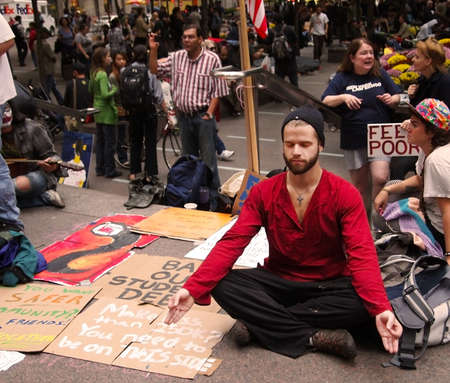 New York - September 21:A young man meditates amid the Occupy Wall St. demonstration near the New York Stock Exchange on September 21, 2011 in New York City.