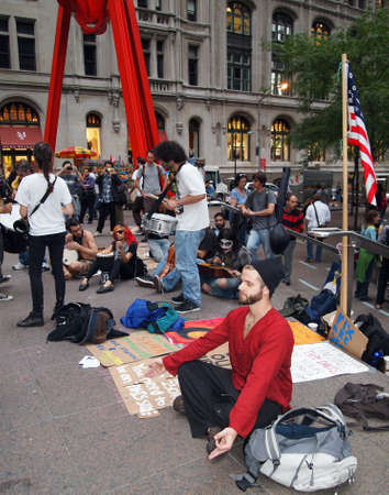 occupy wall street: New York - September 21: A young man meditates amid the Occupy Wall Street demonstration near the New York Stock Exchange on September 21, 2011 in New York City.