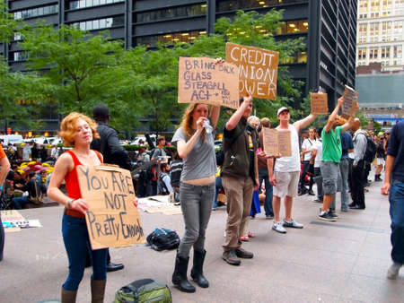 New York - September 21: A group of young people hold signs and shout messages at the Occupy Wall St. demonstration in Zuccotti Park, near the New York Stock Exchange on September 21, 2011 in New York City.