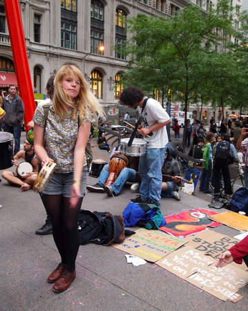 New York - September 21:A young woman plays tambourine amid the Occupy Wall St. demonstration near the New York Stock Exchange on September 21, 2011 in New York City