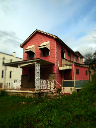 A dilapidated old pink house under a dramatic autumn sky with tilt shift lens effect.