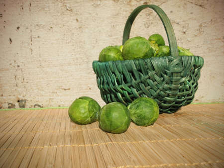 A green basket of fresh green brussels sprouts outside in the sun, against an old stone wall.