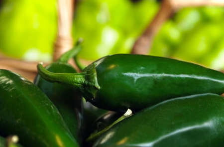 Close-up of hot, green chili pepper in a basket surrounded by more peppers.  Stock Photo