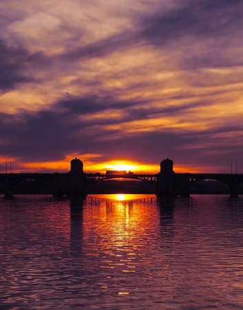 Silhouette of a semi truck crossing a bridge across a bay at sunset  photo