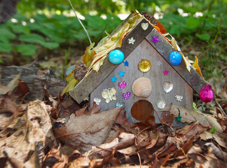 A tiny house hidden in the leaves, and bedazzled with shells, beads, and glass baubles, the home of a faerie  photo