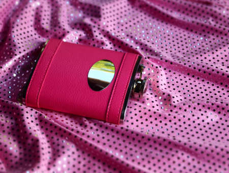 A pink leather covered flask rests in the folds of a pink sequined dress, strewn on the floor Stock Photo - 14389693