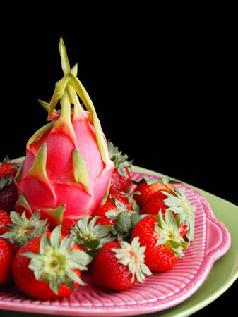 A beautiful and elegant display of strawberries and dragon fruit on a platter isolated on black.