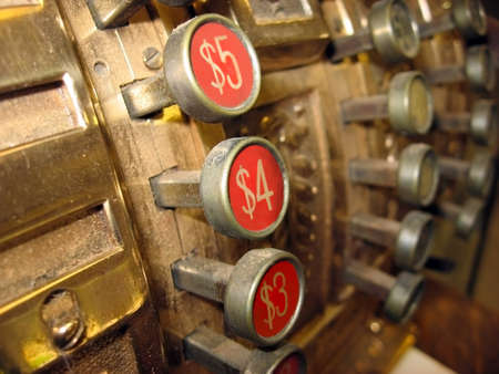 Close up on the knobs of a dusty antique golden cash register  Might represent the concept of