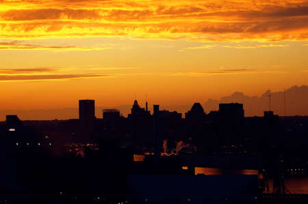 The skyline of Baltimore is viewed in silhouette against a brilliant orange sunset