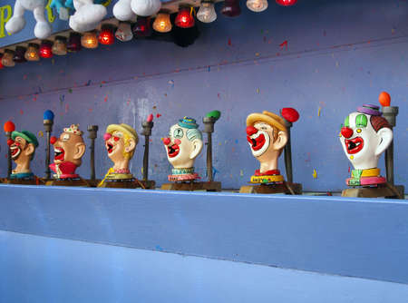 A vintage boardwalk carnival game featuring brightly decorated clown faces with gaping mouths   Editorial