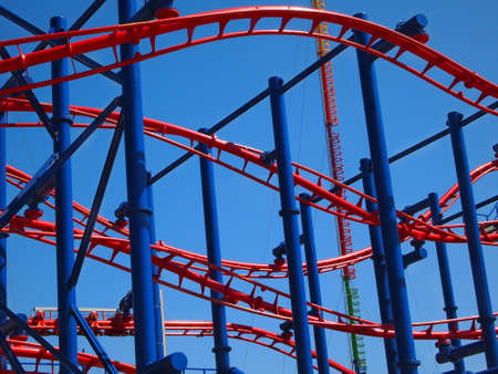 Close up into the tracks of a twisty blue and  red roller coaster against a blue sky.