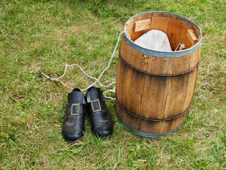 Still life of pilgrim shoes, barrel, and rope for historical reenactment