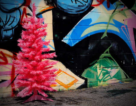 A pink Christmas tree stands in front of a brightly painted graffiti wall in the city  Editorial