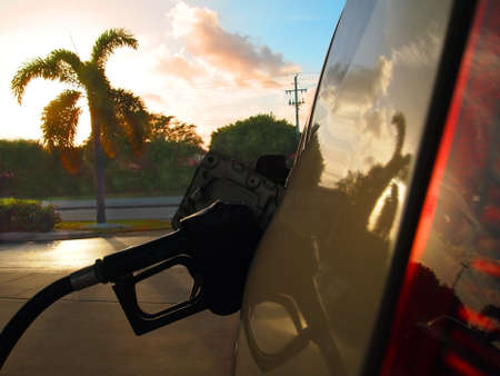 Close up on gas pump, filling the tank of an automobile at sunset with palm tree and colorful clouds in the background  Stock Photo