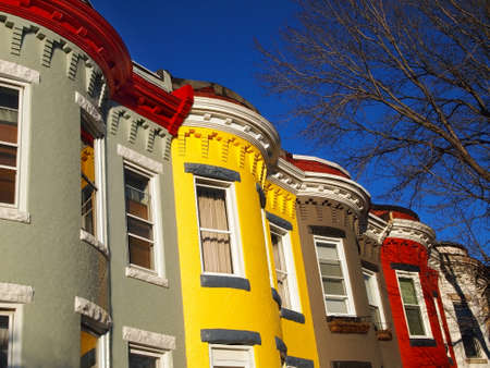 A row of brightly colored, vintage rowhomes in gray, red, yellow, white, and brown, against a brilliant blue sky, with bare winter tree branches  Stock Photo