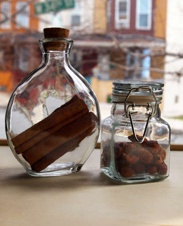 Pretty glass jars containing cinnamon sticks and rosehips displayed in the windowsill with street scene in the background.