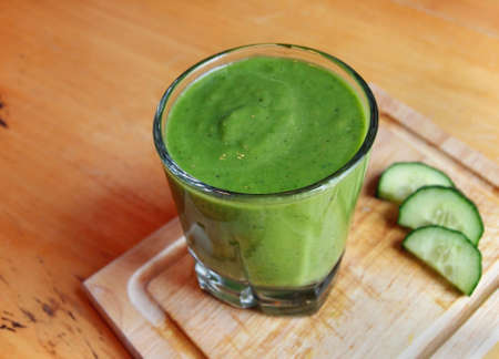 A fresh, green blended smoothie drink on a small cutting board with cucumber slices
