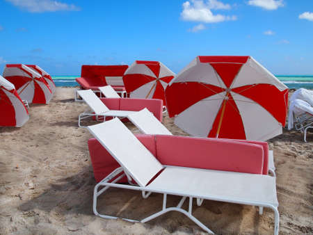 Red and white beach umbrellas and lounge chairs on a sandy beach with brilliant blue water and sky in the background Stock Photo - 19058085