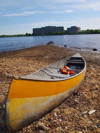 rocky point: Una barca a remi giallo con un giubbotto salvagente siede nel sole del tardo pomeriggio su un promontorio roccioso di terra al porto Archivio Fotografico