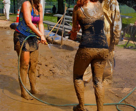 A group of young people hose mud of their bodies with cold water on a hot day in the sunshine.  Stock Photo