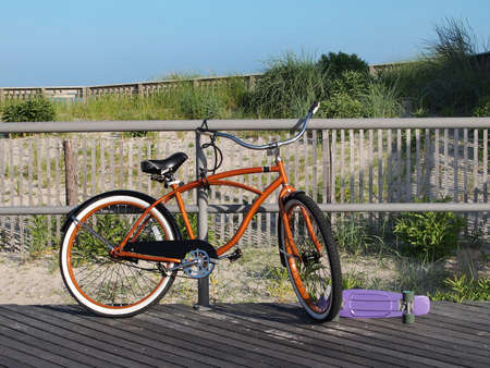 An orange beach cruiser bicycle and a purple skateboard sit on a boardwalk in front of the sand dunes and beach grasses.