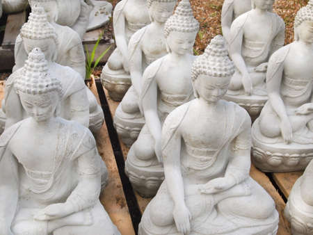 A grouping of cement buddha statues for sale at a garden center.