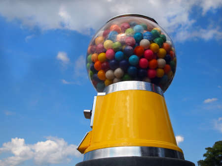 multicolored gumballs: A vintage yellow gumball machine with multi-colored gumballs stands tall in front of a blue sky with wispy clouds.