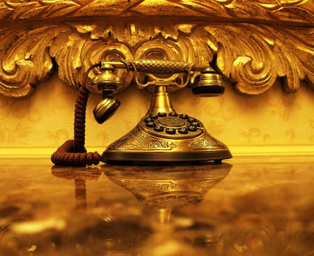 An antique gold telephone and reflection on a shiny marble desktop with vintage style wallpaper and picture frame in the background  photo