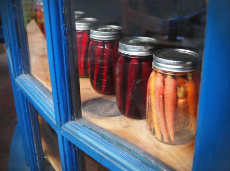 A row of carrots and parsnips pickled in mason jars is displayed in a glass window cabinet with blue frames  photo