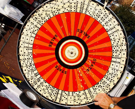 wheel spin: A game of chance spinning wheel outdoors at a fair, with an elderly male hand in the lower corner, taking a spin.  Stock Photo
