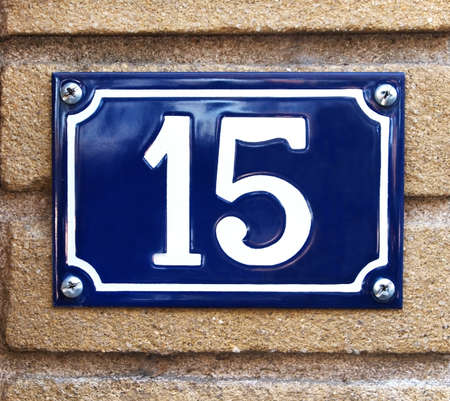 The number 15 in white on a vibrant blue metal plaque screwed to a concrete outdoor wall  photo