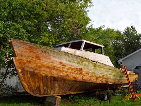 A run down vintage wooden boat propped up on blocks on dry land being repaired. Stock Photo
