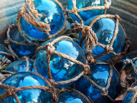 Glass fishing floats with rope knot netting piled in a bucket  Stock Photo