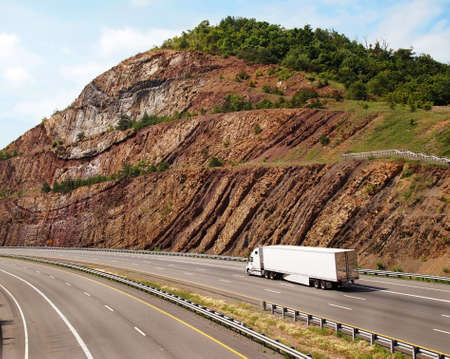 A large white trailer truck drives through a mountain pass with steep sedimentary rock to the sides of the road  photo
