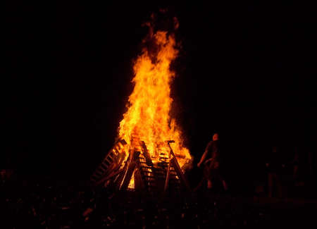 A man throws wood into a glowing red, orange, and yellow bonfire in the dark night