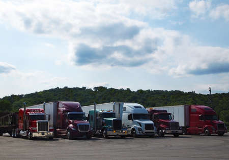 Six  big rig  tractor trailer trucks are parked in a row at mountain top truck stop