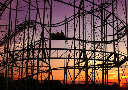 Silhouette of a roller coaster riders with their hands up riding along the track at sunset.