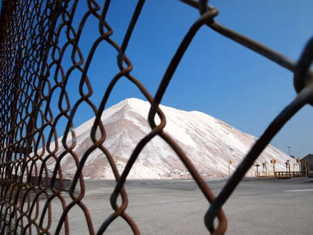 A mountain of road salt sits locked securely behind a chain link fence. photo