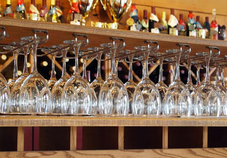 An arrangement of dozens of clean wine glasses hanging in racks in a tasting room at a winery.