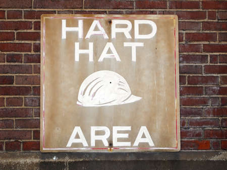 stating: A dingy old sign stating HARD HAT AREA is posted against a brick wall in an industrial space.