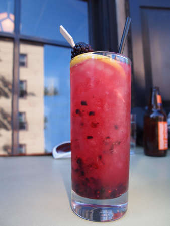 A pink cocktail beverage with fruit and a straw in a tall glass sits on an outdoor cafe table with a blue sky reflecting in the window behind.