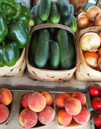 Baskets of cucumbers and peaches, with bell peppers, onions, and apples around the edges, arranged in a display at a local roadside produce stand.