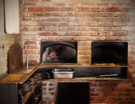 A traditional brick oven with glowing, hot, red coals in a restaurant kitchen with many pans and other cooking implements.