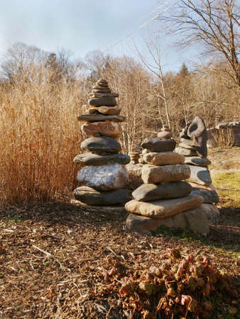 A vertical composition of large stones balanced into towers in a brown winter landscape with dried grasses and leaves.