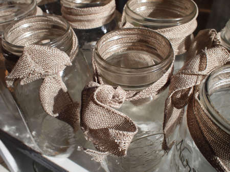 decor: A small grouping of clean, ready to fill, mason jars decorated with simple burlap bows.