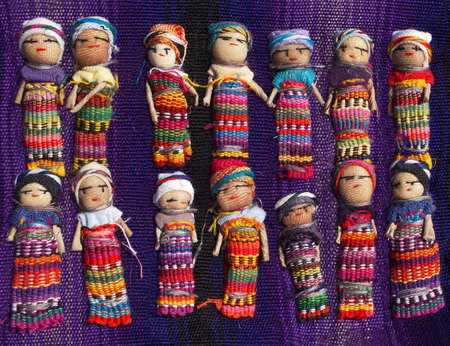 A collection of large, colorful Gautemalan Worry Dolls lined up in two rows on a purple woven blanket.
