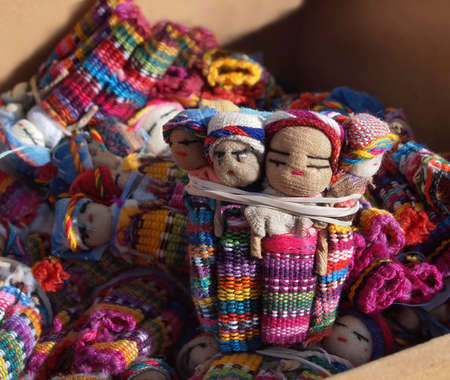 A shipment of colorful Guatemalan Worry Dolls in a cardboard box.