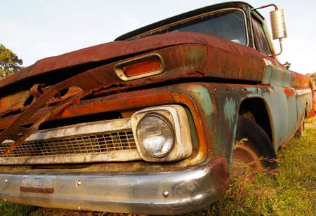 of yesteryear: Extreme closeup of an old, vintage truck rusting away in a grassy field.